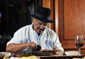 image of tobaco leaf  - older senior man making luxury handmade cuban cigare - JPG