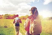 travel, hiking, backpacking, tourism and people concept - couple with backpacks walking along countr poster