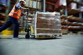 Blurred motion shot of warehouse worker wearing hardhat and reflective jacket pushing moving cart wi poster