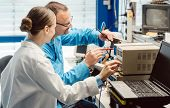 Team of electronic engineers testing a product prototype on test bench in the lab poster