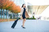 Travel. Business Woman In Airport Talking On The Smartphone While Walking With Hand Luggage In Airpo poster