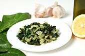 A side dish of swiss chard cooked in olive oil with garlic and chili flakes and then tossed in lemon