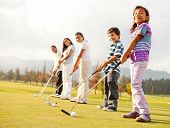 Golf players of all ages practicing to hit the ball at the course
