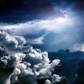Light In The Dark And Dramatic Storm Clouds poster