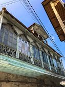 Old Carved Beautiful Antique Balcony Of A Wooden European House. European Old Architecture. Vertical poster
