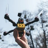 Pilot Racing Drone Holds In His Hand Fpv Copter Before Launching It. A Small High-speed Aircraft Wit poster