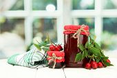 jars with hip roses jam and ripe berries, on wooden table