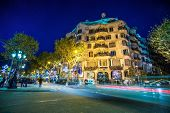 BARCELONA-NOVEMBER 24: La Pedrera or Casa Mila at dusk, built and designed by Antoni Gaudi, with tra