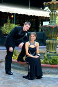 image of night gown  - Teen couple sit outdoors at a water fountain dressed and ready for their high school prom night. Tux and gown both in black.  ** Note: Slight graininess, best at smaller sizes - JPG