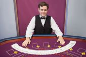 Smiling dealer with fanned out deck of cards in casino