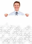 Confident Business Man Holding A White Puzzle Board For Copy-Space