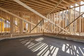 stock photo of 2x4  - New house interior framing with garage floor freshly poured - JPG