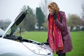 picture of truck-stop  - Caucasian woman calling for road side assistance on her mobile phone - JPG