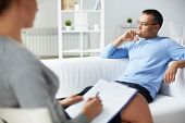 stock photo of psychology  - Pensive man trying to relax on sofa during psychological therapy session - JPG