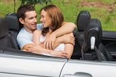 Couple in love cuddling in the backseat and chatting in convertible