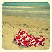picture of a red swimsuit laying on the sand of a beach, with a frame and a retro effect