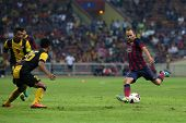 KUALA LUMPUR - AUGUST 10: FC Barcelona's Andres Iniesta (maroon/blue) kicks the ball in a friendly match vs Malaysia at the Shah Alam Stadium on August 10, 2013 in Malaysia. Barcelona wins 3-1.