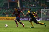 KUALA LUMPUR - AUGUST 10: Barcelona's Adriano (maroon/blue) dribbles past Malaysia's Mahalli Jasuli (2) in a game at the Shah Alam Stadium on August 10, 2013 in Malaysia. Barcelona wins 3-1.