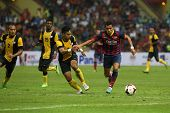 KUALA LUMPUR - AUGUST 10: FC Barcelona's Alexis Sanchez (maroon/blue) takes on Malaysia's MA Zafuan (7) at the Shah Alam Stadium on August 10, 2013 in Malaysia. FC Barcelona wins 3-1.