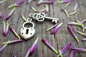 stock photo of lock  - Key with heart shaped lock charm on wooden background - JPG