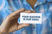 stock photo of helpdesk  - A person holding a white card with the words Your success is our goal - JPG
