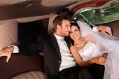 image of limousine  - Happy couple sitting in limousine on wedding - JPG