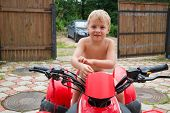 Little boy on a quad bike stands in the yard at home