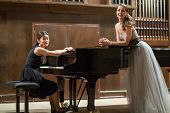 Woman pianist sits at the piano and beautiful singer stands next