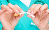 Doctor in uniform breaks cigarette, quit smoking concept, isolated over white