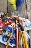 stock photo of bute  - Art palette with a lot of paints and paintbrushes - JPG