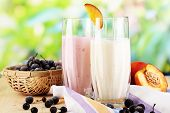 Delicious milk shakes with blackberry and peach on wooden table on natural background