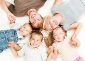 Happy Big Family Portrait. Father, Mother, Daughter and Sons Together Lying on floor and Holding Han