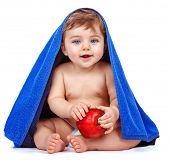 Cute baby boy covered with blue towel holding in hands red fresh apple, sweet child after bath, healthy lifestyle, kids nutrition, happy childhood concept
