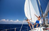 Happy couple having fun on sailboat, young family in water cruise, yachting sport, active lifestyle,