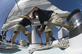 stock photo of watersports  - Low angle view of sailors operating windlass on yacht - JPG