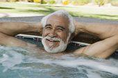 Happy senior man relaxing at the edge of swimming pool
