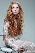 A portrait of stylish elegant redheaded girl is in lace clothes