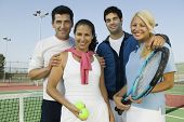 Portrait of confident mixed doubles tennis players with rackets and balls on court
