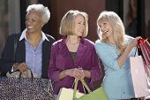 Happy multiethnic female friends with shopping bags