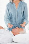 Female therapist performing Reiki over face of senior man at health spa