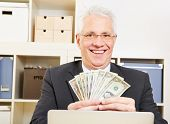 Happy eldery business man with fan of dollar bills in the office
