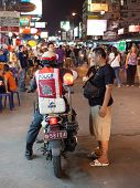 BANGKOK, THAILAND - JANUARY 9, 2012: Local man talks on the street with policeman on the motorcycle