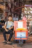 BANGKOK, THAILAND - JANUARY 9, 2012: Young man sells water and juices on Khao San Road food stall. E