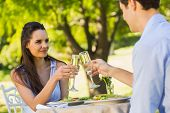 Smiling young couple toasting champagne flutes at an outdoor caf�?�©