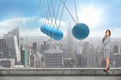 picture of newton  - Smiling thoughtful businesswoman against newtons cradle above city - JPG