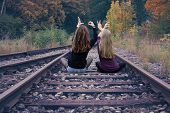 Two Girls Sitting On Railway Tracks And Write Love