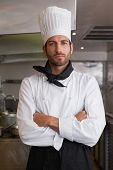 Serious head chef looking at camera with arms crossed in a commercial kitchen