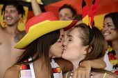 Cheerful couple of German lesbian soccer fans kissing each other celebrating victory.