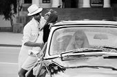 Young couple in love and jealous girl in retro car
