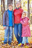 Mother and her two children stand having embraced in autumn park near tree trunk